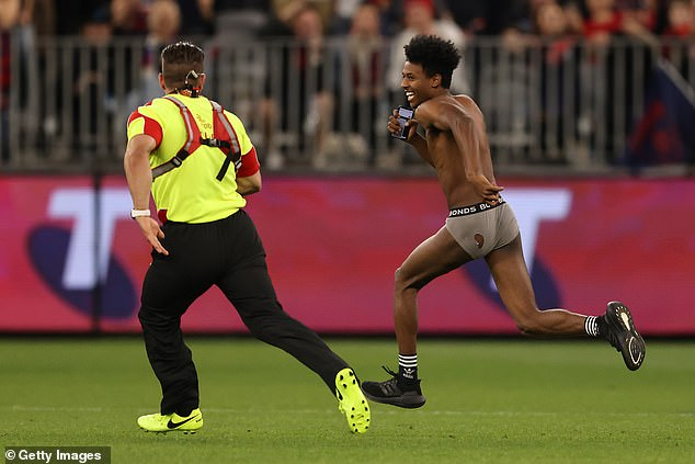 Daring pitch invader storms the field during the AFL Grand Final as Demons close in on premiership